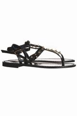 Sandale plate avec une bride cloutée. Se ferme avec une