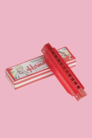 Red toy harmonica in a box. Material: Metal,Card,Plastic